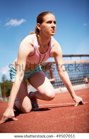 Image of young female ready to start running while on stadium
