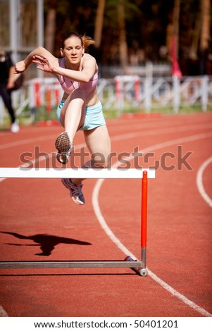 Image of young female running and getting ready to jump over barrier - stock photo