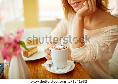 Image of young female with cup of latte sitting in cafe - stock photo
