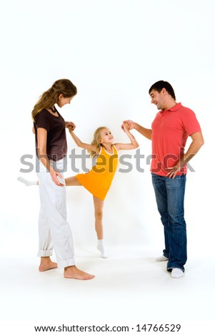 Image of young girl doing exercise holding her parents by hands