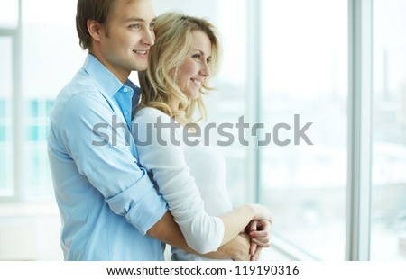 Image of young guy embracing his girlfriend and both looking through window - stock photo