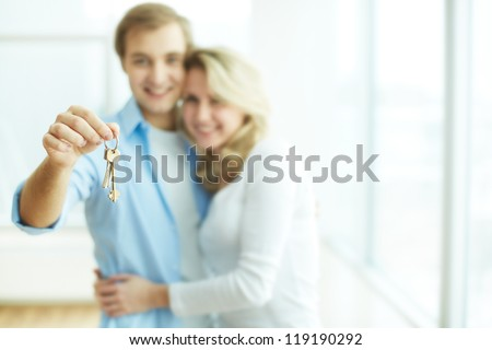 Image of young happy couple embracing while man showing key from new flat - stock photo