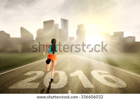 Image of young healthy woman wearing sportswear and running on the road with numbers 2016 - stock photo