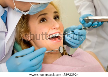 Image of young lady with dentist over her before checking oral cavity - stock photo