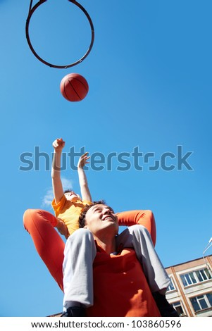 Image of young man and his son playing basketball - stock photo