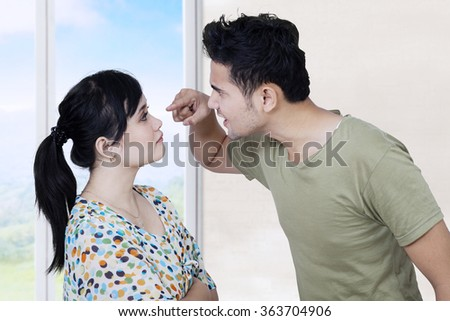 Image of young man quarreling with his wife at home while screaming and scolding his wife - stock photo