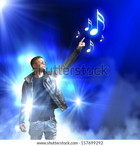 Image of young man rock musician in lights - stock photo