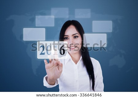 Image of young pretty businesswoman pressing button with numbers 2016 on the virtual screen - stock photo