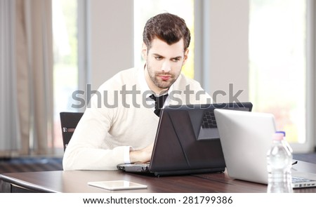 Image of young sales man sitting at office in front of laptop and working on business plan.