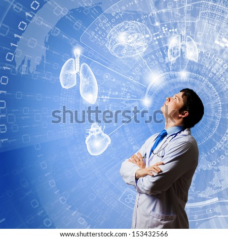 Image of young thoughtful doctor looking at media screen - stock photo