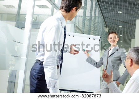 Image of young woman explaining ideas on whiteboard at meeting - stock photo