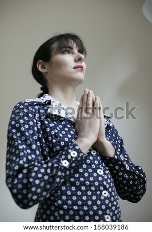 image of young woman in dotted dress with prayer , woman with hands in prayer , image of young woman having prayer  - stock photo