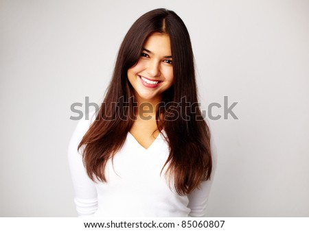 Image of young woman in white pullover smiling at camera - stock photo