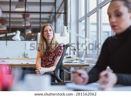 Image of young woman sitting at her desk looking away thinking. Female executive in office lost in thought. - stock photo