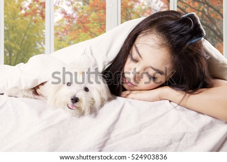 Image of young woman sleeping in the bedroom with her puppy under blanket, shot at home