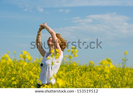 Image of young woman standing in yellow rapeseed field - stock photo