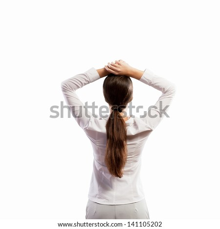 Image of young woman standing with her back with arms above head. Place for text - stock photo