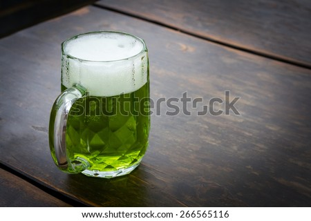 Image on an unusual green beer on wooden table. This beer is traditionally served on St. Patrick's day, but also during Easter time in Central Europe. It is lager mixed with extract from herbs. - stock photo