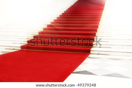 Image on the staircase with red carpet, illuminated by light - stock photo