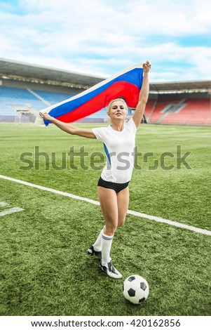 Image or photo of young adult sporty girl hold in hands Russian flag and white and black ball  on green grass near sexy legs. Goalkeeper woman or football fan stand against stadium seat. russian flag - stock photo