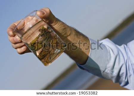 Image showing a hand holding a test beaker with an environmental sample. - stock photo