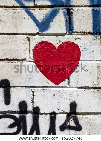 Image showing a red heart, with blue and black spraypaint, graffitied onto a white brick wall. - stock photo