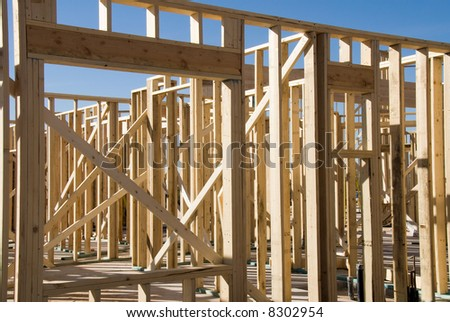 Image shows a home under construction at the framing phase.  Ideal for new construction advertising and other home construction promotional inferences - stock photo