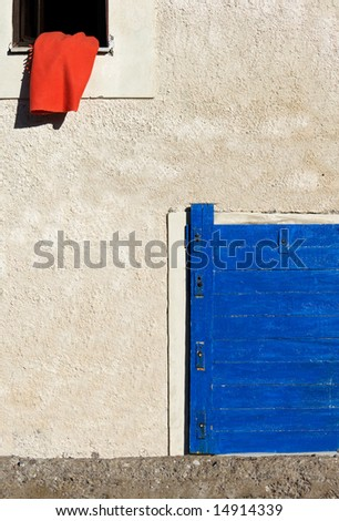 Image shows a red blanket on the window of a Greek village house. A blue door appears in the lower right corner - stock photo