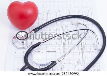 Image shows a red rubber heart with stethoscope and cardiogram - stock photo