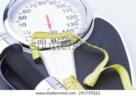 Image shows a scale, measuring tape and a dumbell - stock photo