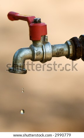 Image shows a tap dripping water against a dry background - stock photo