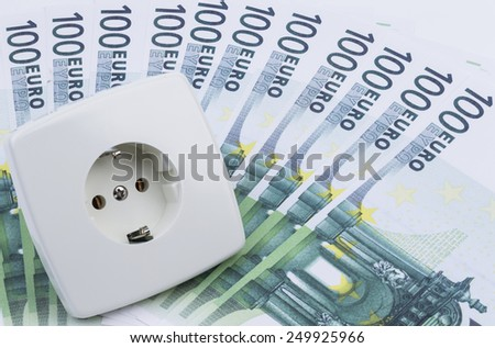 Image shows a white power socket with some banknotes - stock photo