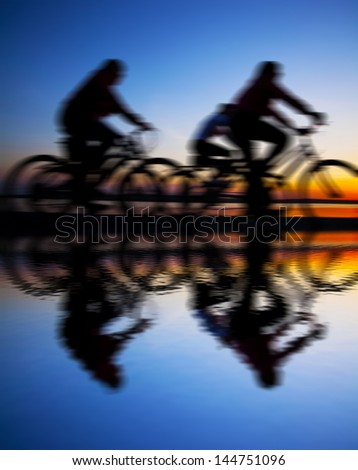 Image sporty company friends on bicycles outdoors against sunset Silhouette with reflection on water . A lot phases of motion of a single cyclist along shoreline coast copy Space for inscription - stock photo
