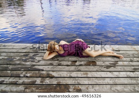 Images of a beautiful red-haired girl on the pier in a purple dress - stock photo