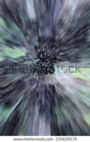 Imaginary pointillist abstract of a cluster of black holes, like the head of a dark flower, with radial blur to simulate distortion of travel at speed faster than light - stock photo