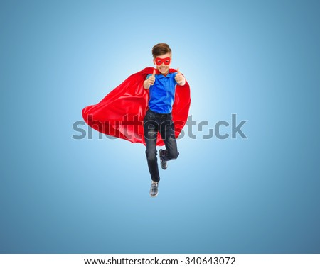 imagination, gesture, childhood, movement and people concept - boy in red super hero cape and mask flying in air and showing thumbs up over blue background - stock photo