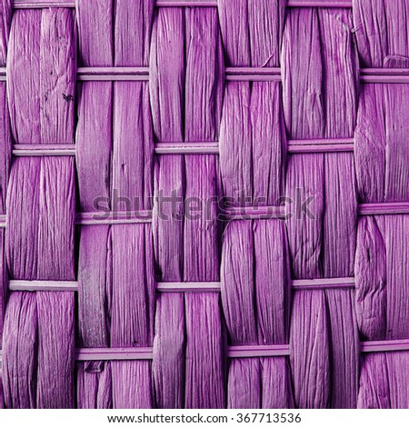 Imaginative pink / lilac / purple woven reed / wood / wooden abstract background texture, weaving crisscross pattern. - stock photo