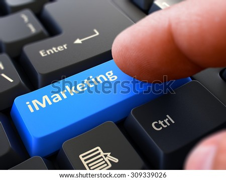 IMarketing Button. Male Finger Clicks on Blue Button on Black Keyboard. Closeup View. Blurred Background. - stock photo