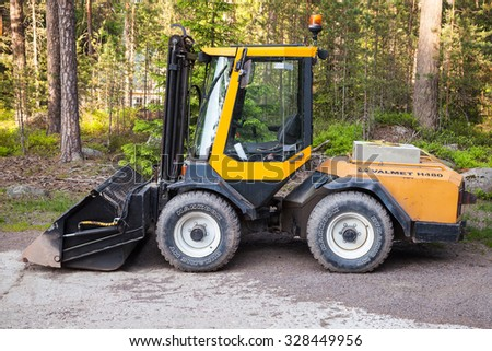 Imatra, Finland - June 11, 2015: Yellow forklift Valmet H480 with general bucket stands on a logging area