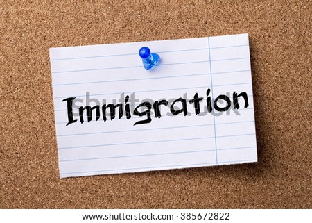 Immigration - teared note paper pinned on bulletin board - horizontal image - stock photo