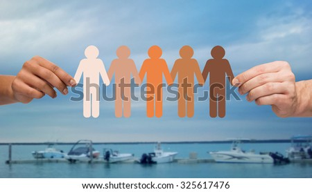 immigration, unity, population, race and humanity concept - multiracial couple hands holding chain of paper people pictogram over boats in sea background - stock photo