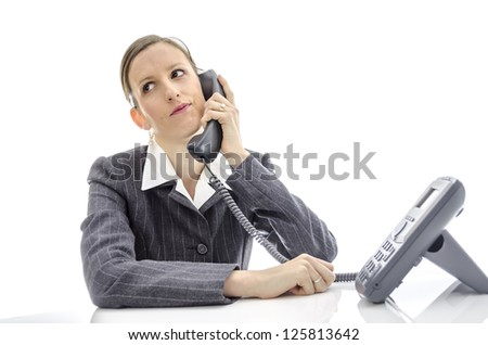 Impatient business woman at white desk making a phone call. - stock photo