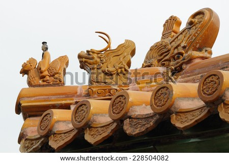 Imperial roof decoration of a minor building ,At the head of the procession  a man riding a Phoenix and the imperial dragon,Summer Palace in Beijing, China, Asia - stock photo