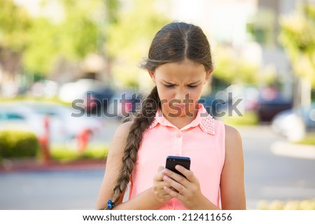 Important text message. Portrait teenage girl looking concerned with text message on her phone, isolated outdoor street background. Human face expressions, emotions, body language, reaction, feelings - stock photo