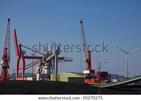Imported coal alongside a wind turbine at the Port of Bristol Avonmouth docks UK - stock photo