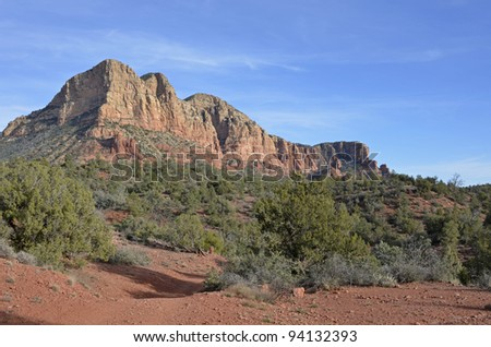 Imposing and majestic red rock cliffs and mesas contrast with deep green vegetation in scenic Sedona, where mystery is palpable and the natural beauty, overwhelming. - stock photo