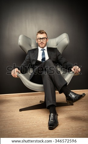 Imposing mature man in elegant suit sitting on a leather chair in a modern luxurious interior. Fashion. Business. - stock photo