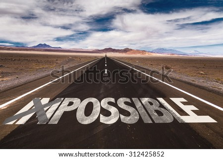 Impossible/Possible written on desert road - stock photo