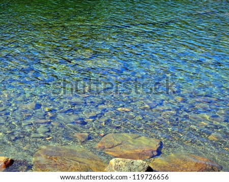 Impressionistic image of sunlight playing over the water's surface on Jordan Pond in Acadia, creating webs and spangles of light in an abstracted realism composition.
