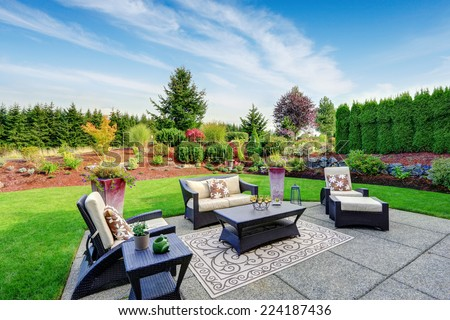 Impressive backyard landscape design. Cozy patio area with settees and table - stock photo